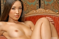 Tiny Asian model gets naked in a big chair